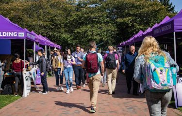 Students Walking Nearby Several Canopies on Campus